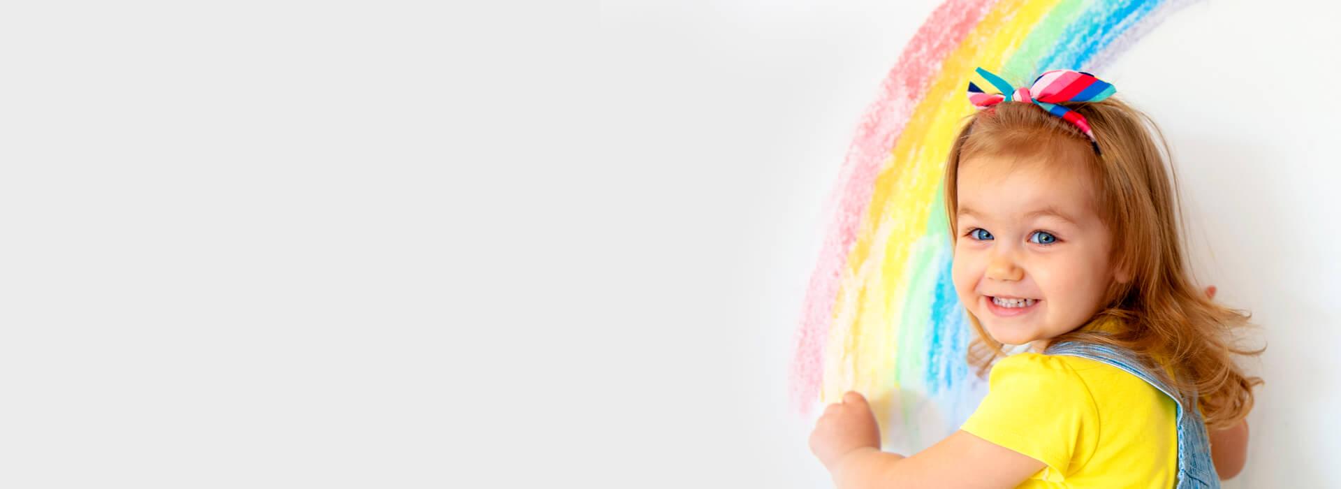 Meisje dat een regenboog tekent op de muur