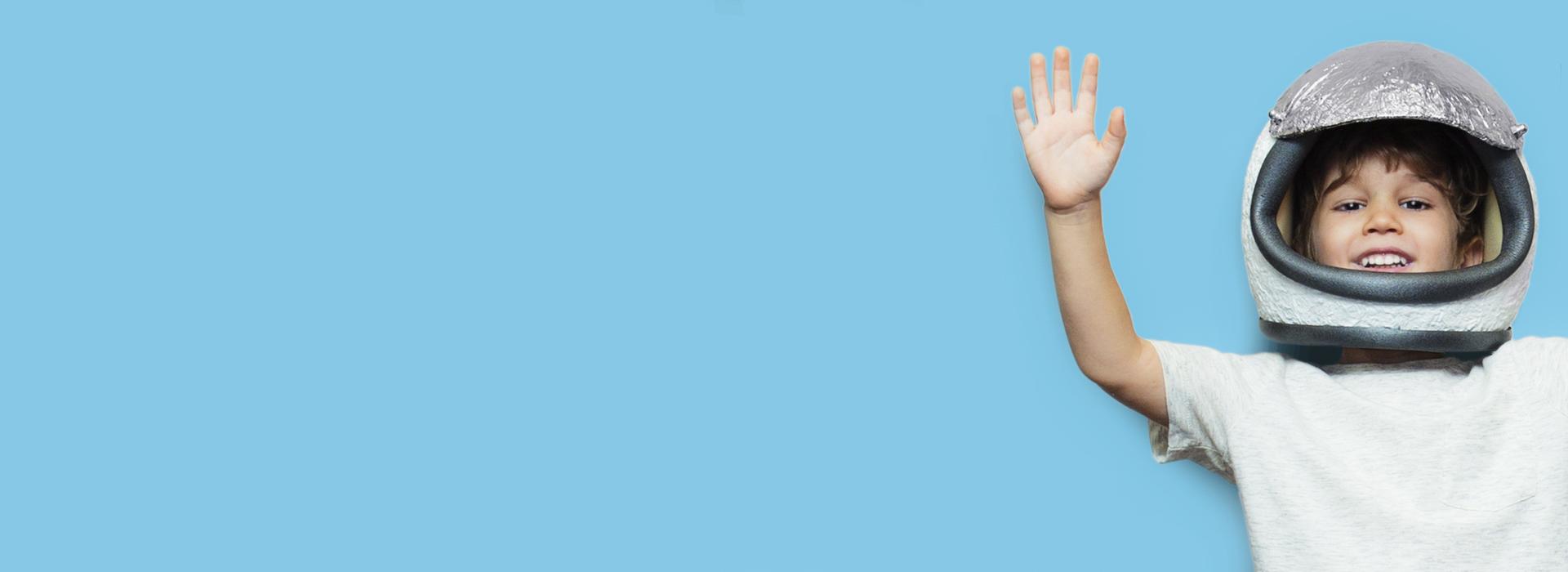 Jongen met ruimtehelm zwaait met zijn hand