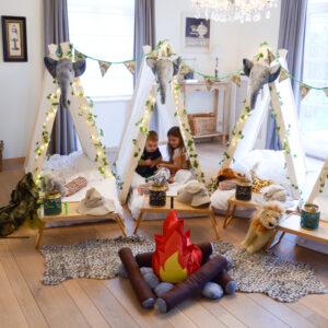 Jongen en meisje spelen in de tipi tent tijdens een jungle thema slaapfeestje
