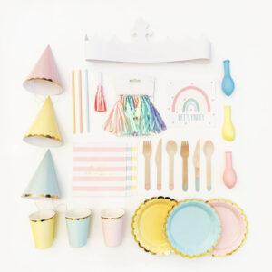 kinderfeestje-thema-regenboog-gekleurede-pastel-feesthoedjes-pastel-bordjes-pastel-bekers-pastel-rietjes-pastel-servietten-gekleurde-slingerbestek-witte-kroon-roze-feesttoeters-uitnodiging
